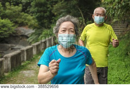 Senior Couple Wearing Face Mask And Walking Trough Nature Park