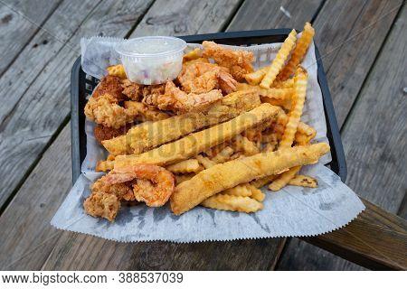Junk Food Seafood. Crispy Fish, Shrimp, And Chips. Fried Seafood, French Fries, Lemon Slices In Disp