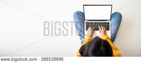 Top View Of Woman Sitting On Floor And Using Laptop Blank Screen White Background. Mockup, Template