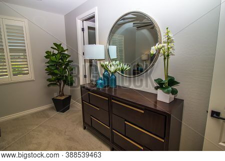Bedroom With Wooden Dresser, Wall Mirror And Decorator Items