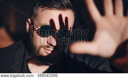 Bearded Caucasian Man Is Posing With Glasses While Trying To Cover The Sun Light Warming His Face Wi