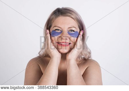 Close Up Photo Of A Caucasian Woman Wearing Hydrogel Eye Patches And Smile At Camera With Naked Shou