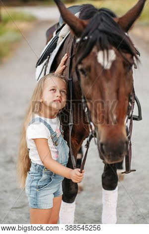 Friendship Of A Child With A Horse. Treating Autism With A Horse. Interaction Of A Girl With Autism