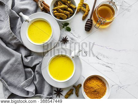 Yellow Turmeric Latte Drink. Golden Milk With Cinnamon, Turmeric, Ginger  And Honey Over White Marbl