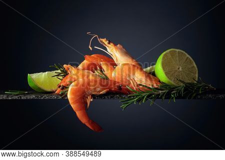 Shrimps With Rosemary And Lime On A Black Background. Copy Space.