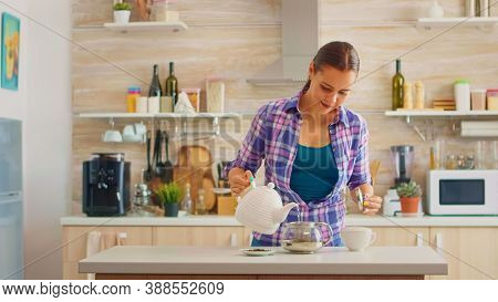 Happy Housewife Pouring Hot Water In Teapot To Prepare The Green Tea For Breakfast In The Morning. M