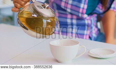Close Up Of Tea From The Kettle Slowly Pour Into Porcelain Cup. Young Lady Preparing Green Tea In Th