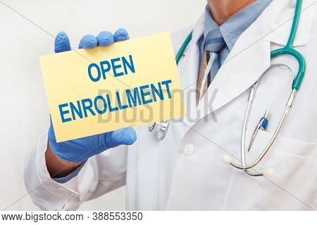 Close-up Of A Male Doctor In Gloves Holding A Sign With The Text Open Enrollment. Medical Concept