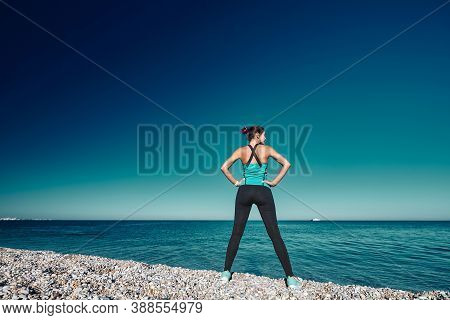 Female Having Workout On Coastline. Fresh Air And Blue Cloudless Sky. Active Lifestyle And Fitness C