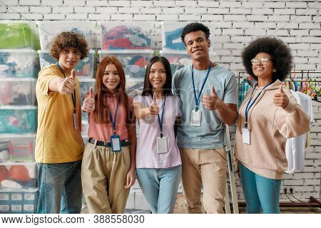 Young Diverse Volunteer Group Smiling At Camera, Showing Thumbs Up While Posing In Front Of Boxes Fu