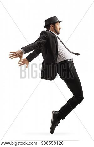 Full length profile shot of a man in a suit and hat dancing on tiptoes isolated on white background