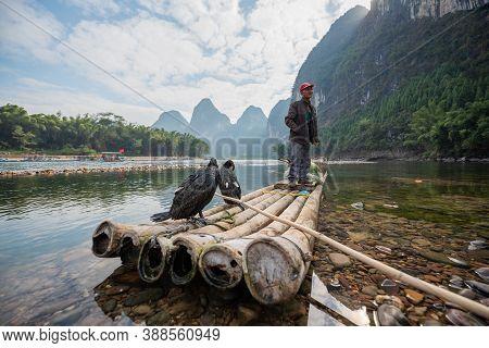 Yangshuo, Guilin, Guangxi Province, China - November 12, 2019: Cormorant Fisherman Standing On His B