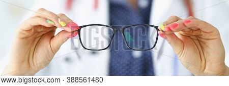 Woman In White Medical Coat Holds Glasses In Her Hands. Vision Diagnostics By An Optometrist Concept