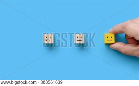 The Customer Hand Picked The Wooden Block With Happy Face Smile On Blue Background. Service Rating ,