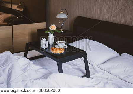 Happy Morning. Breakfast In Bed On Tray Table With Coffee And Croissant And Rose In Vase, Wooden Int