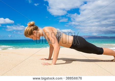 Attractive Young Woman Doing Push Up Exercise on the Beach���