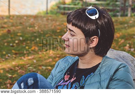 Young Brunette Woman With Short Hair In A Profile Thoughtfully Looks Aside On The Background Of Gras