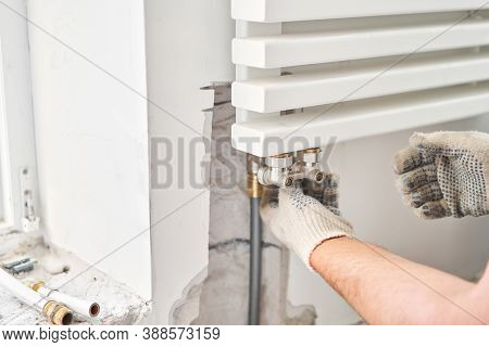 Work As A Plumber, Mounting Water Heating Radiator On The White Wall Indoors. Connection Heating Pip