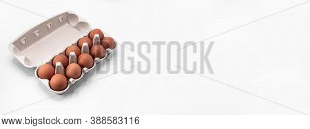 Overhead View Of Brown Chicken Eggs In An Open Egg Carton Isolated On White Background. Fresh Chicke