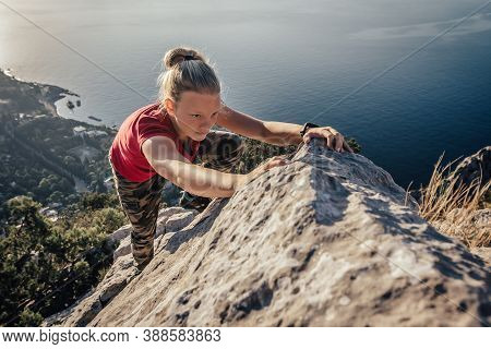 Young Strong Girl Climbs To Top Of Cliff. Overcoming Obstacles And Courage. Ambitious Climber Climbi