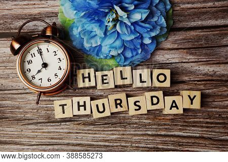 Hello Thursday Alphabet Letters With Alarm Clock And Blue Flower On Wooden Background