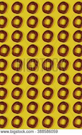 Food Pattern. Repetition Of The Silhouette Of Freshly Baked Round Bagels On A Yellow Background. Bro