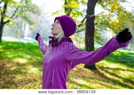 Enjoying the nature. Young woman arms raised enjoying the fresh air in green forest.