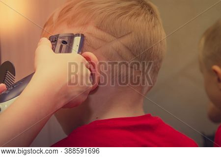 The Spider-man Symbol Is Shaved With A Typewriter On The Child's Head. Haircut Drawing On The Boy's