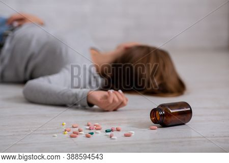 Young Woman Committing Suicide By Overdosing On Pills, Focus On Bottle Of Tablets Scattered On Floor