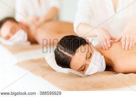 wellness, bodycare and health concept - couple wearing face protective medical mask for protection from virus disease having back massage at spa