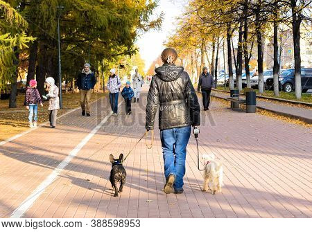 Russia, Chelyabinsk, October 04, 2020: Girl Walks With The Dogs Along The City Street. Black And Whi