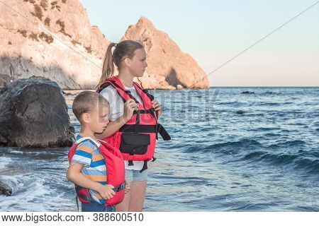 Children Stand On Seashore In Red Life Vests And Look At Stormy Sea. Safety Of People On Water. Life