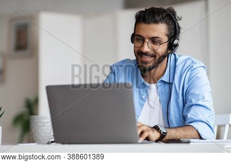 Hotline Operator. Portrait Of Indian Customer Support Manager Man In Headset Working With Laptop Com