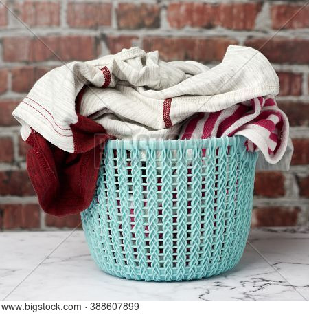 Laundry Basket And Folded Laundry, Brown Brick Wall Background, Close Up