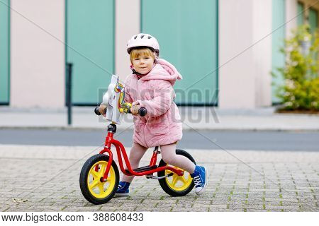 Cute Little Toddler Girl With Helmet Riding On Run Balance Bike To Daycare, Playschool Or Kindergard