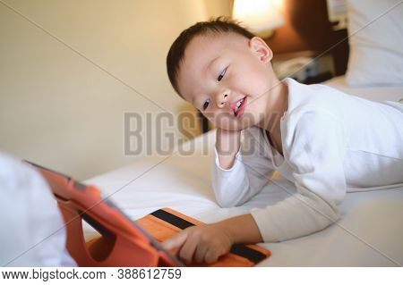Cute Little Asian 2-3 Years Old Toddler Boy Child Sitting In Bed Watching A Video From Tablet Pc. Ki