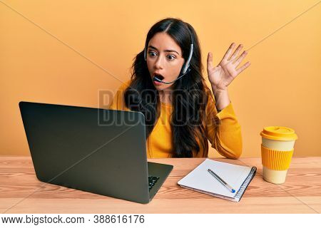 Beautiful brunette young woman wearing call center agent headset afraid and shocked with surprise and amazed expression, fear and excited face.