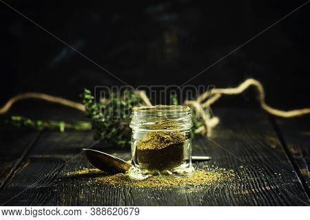Traditional Caucasian Seasoning With Herbs And Spices, Khmeli Suneli In A Glass Jar, Black Backgroun