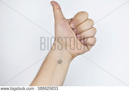 The Man Shows His Hand With A Chip Implanted. The Fist Is Compressed Into A Like. The Concept Of App