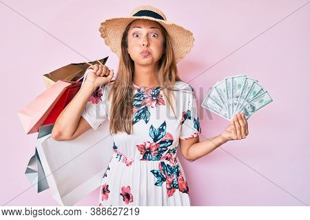 Middle age hispanic woman holding shopping bags and dollars puffing cheeks with funny face. mouth inflated with air, catching air.