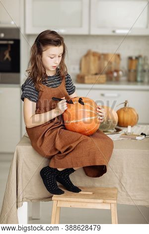 Little Girl Paints A Pumpkin For Halloween. Preparation For Halloween. Halloween Holiday And Family