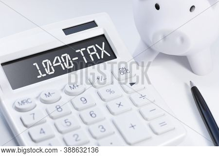 Word 1040-tax On Calculator. Business And Tax Concept On White Background. Top View.
