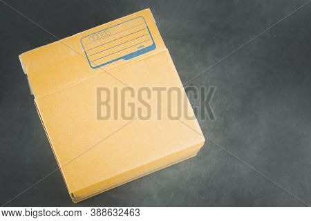 Small Packet Of Brown Box With Empty For Write Address Sender On Black Background.