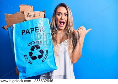 Young beautiful blonde woman recycling holding paper recycle bag full of paperboard pointing thumb up to the side smiling happy with open mouth
