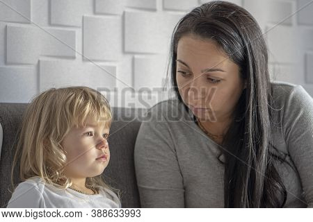 Mom Talking To Her Little Daughter On The Couch. Concept: Children's Whims And Tantrums, Formation O