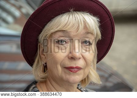 Street Portrait Of An Elderly Woman In A Fashionable Hat On The Background Of City Buildings, Close-