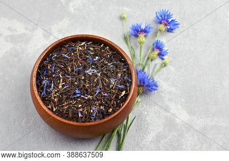 Blend Of Black Tea, Cornflowers Petals And Thyme In Wooden Bowl With Fresh Blue Cornflowers