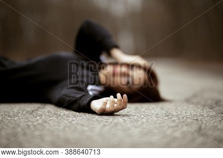 Young Woman Laying On The Ground Middle Of Road Reaching Out
