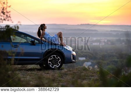 Happy Young Woman In Blue Dress Sitting On Her Vehicle Bonnet Looking At Sunset View Of Summer Natur