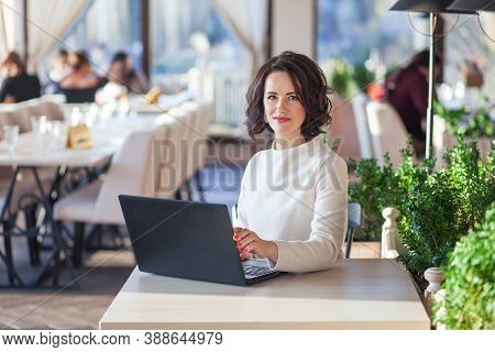 Adult Elegant Businesswoman In White Dress Sitting With Laptop In Cafe. Beautiful Brunette Lady Usin